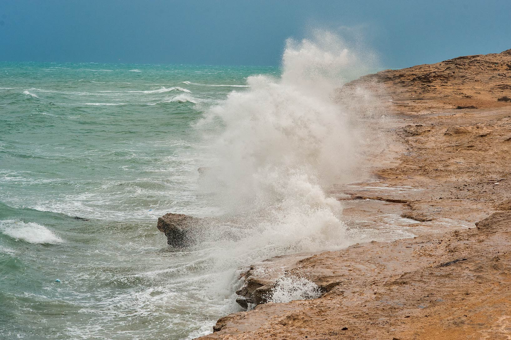 Waves on a beach near Jebel Fuwairit at windy day. Northern Qatar