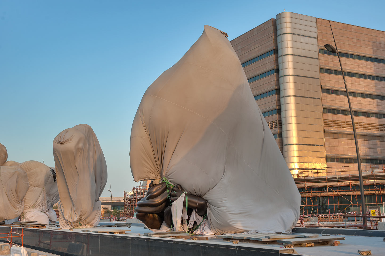 "Drape bags hiding ""Miraculous Journey"" sculptures...and Research Center. Doha, Qatar"