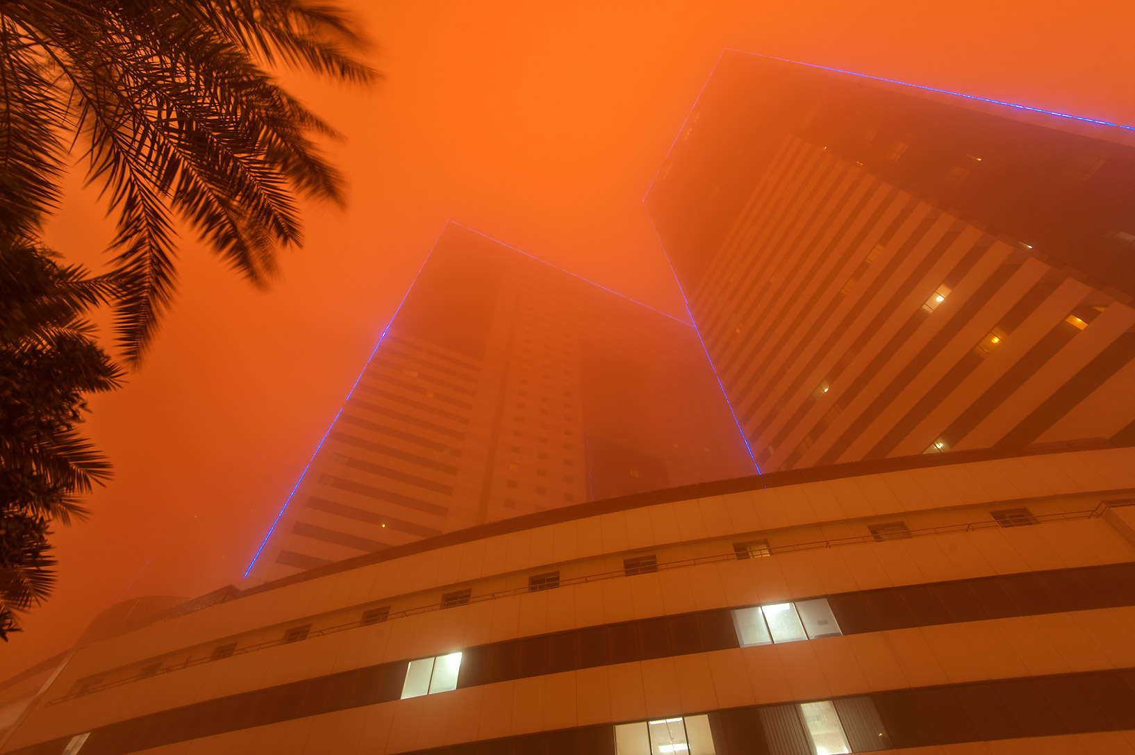 Towers No. 1 and 3 of Ezdan Hotel and Suites in...light from a dust storm. Doha, Qatar