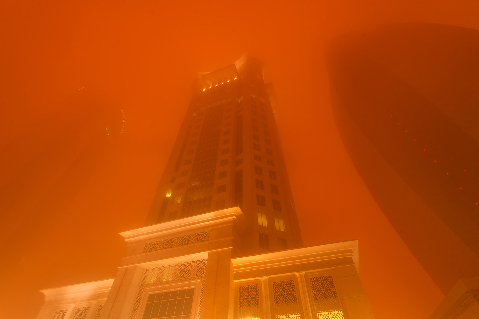 Al Gassar Tower in West Bay in orange light from a dust storm. Doha, Qatar