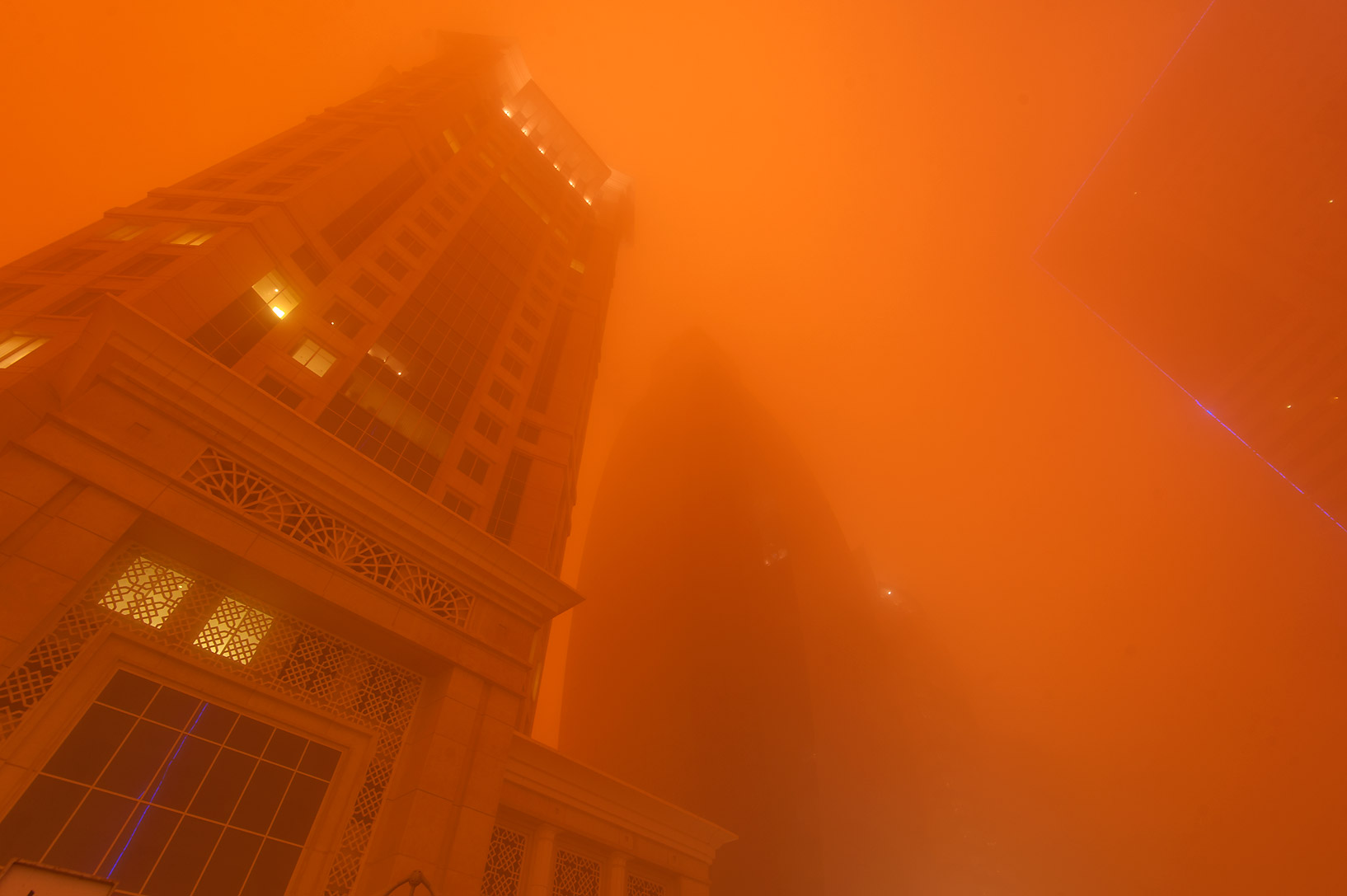 Al Gassar Tower in West Bay in orange light from dust. Doha, Qatar