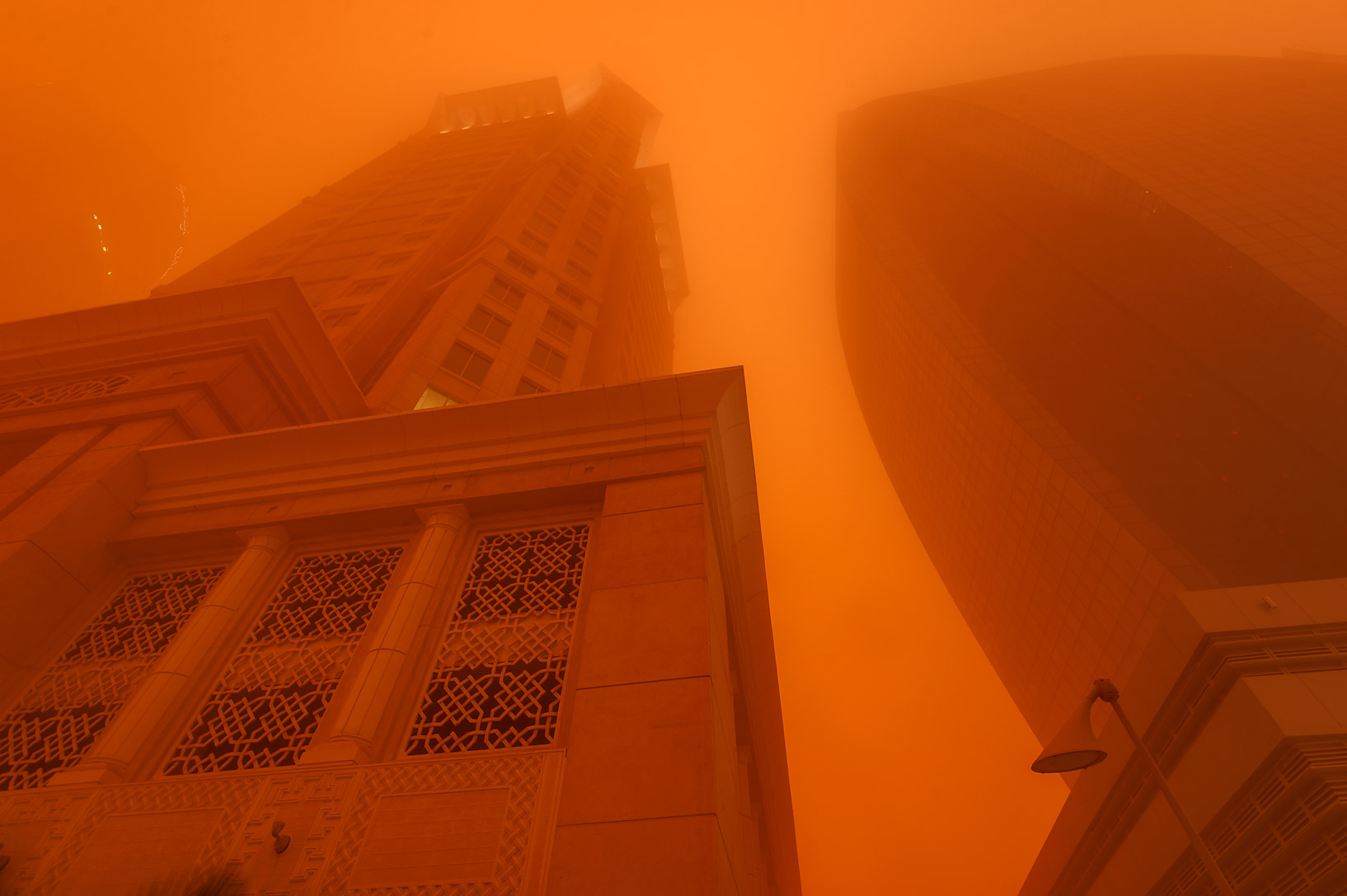 Al Gassar and Al Huda Engineering Works towers in West Bay in orange dust. Doha, Qatar