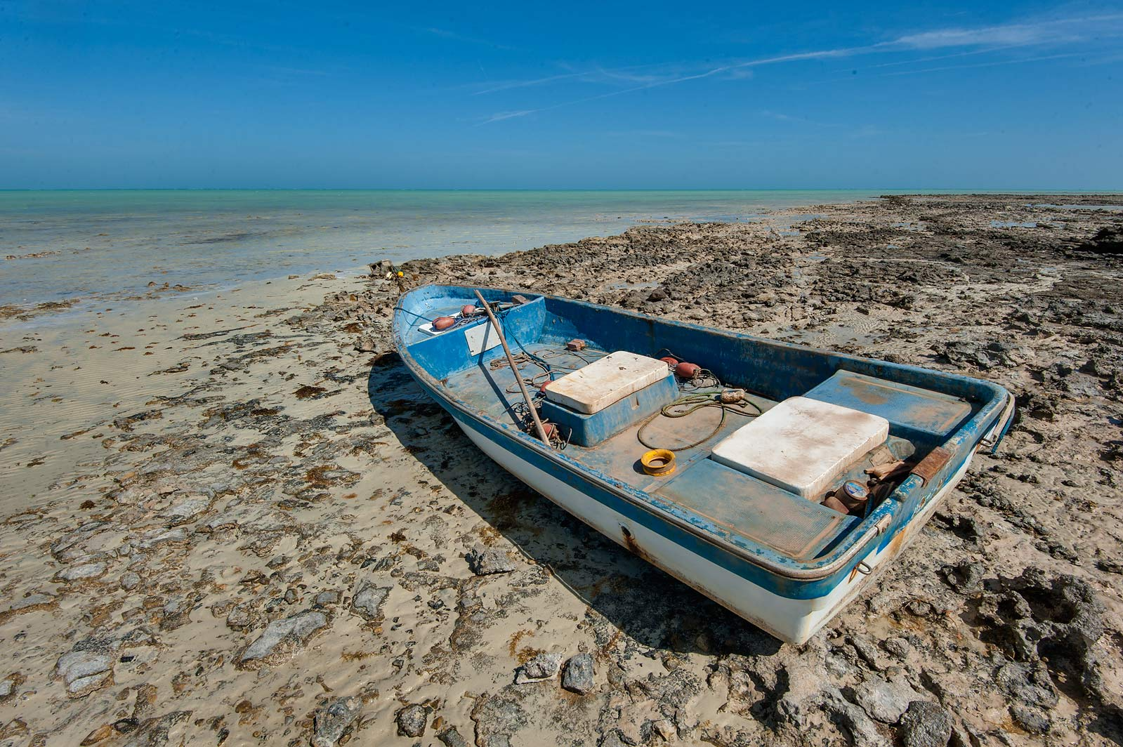 Boat at low tide on a small peninsula. Ruwais, Northern Qatar