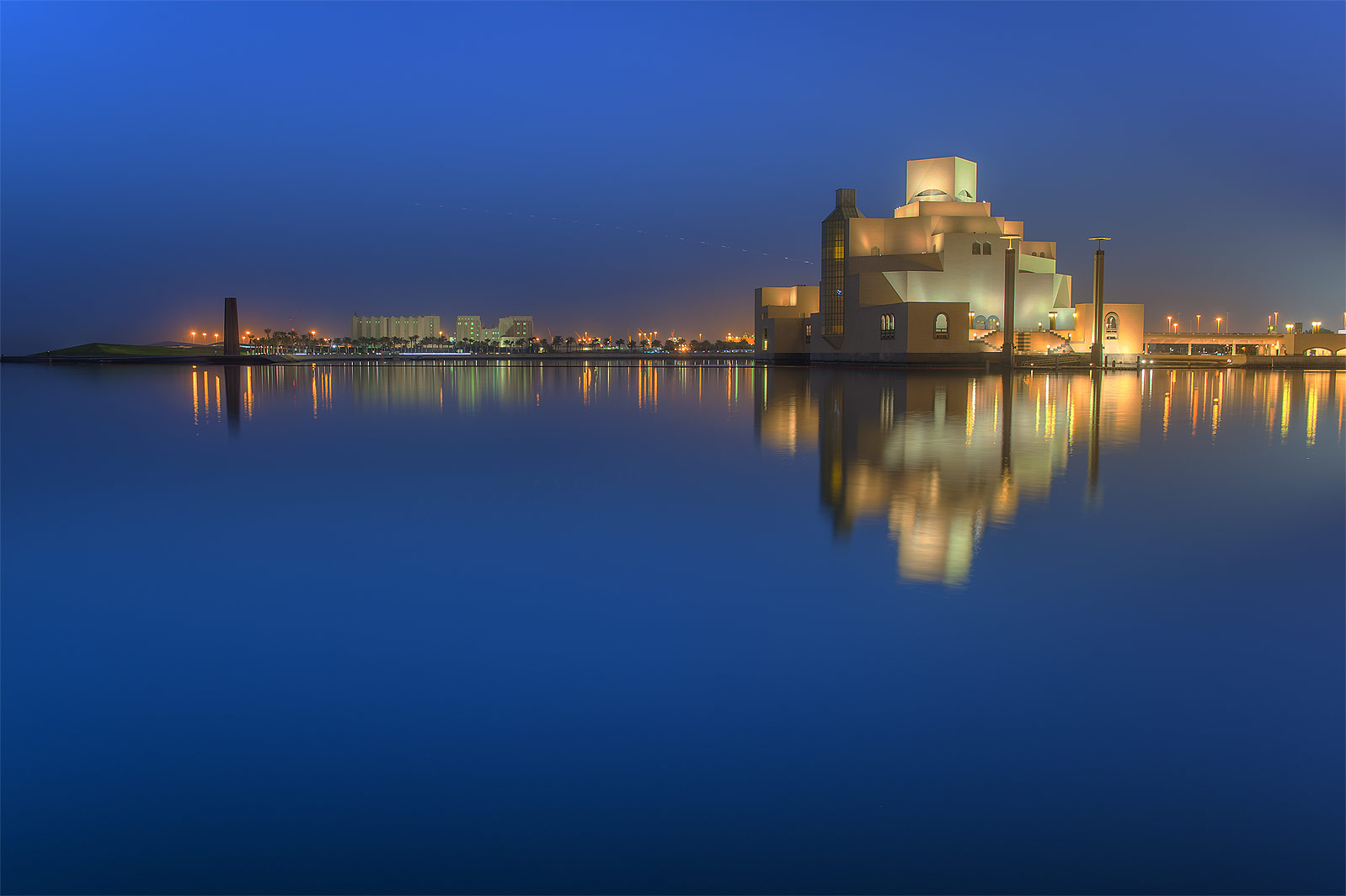 Reflections of Museum of Islamic Art from a boat pier. Doha, Qatar