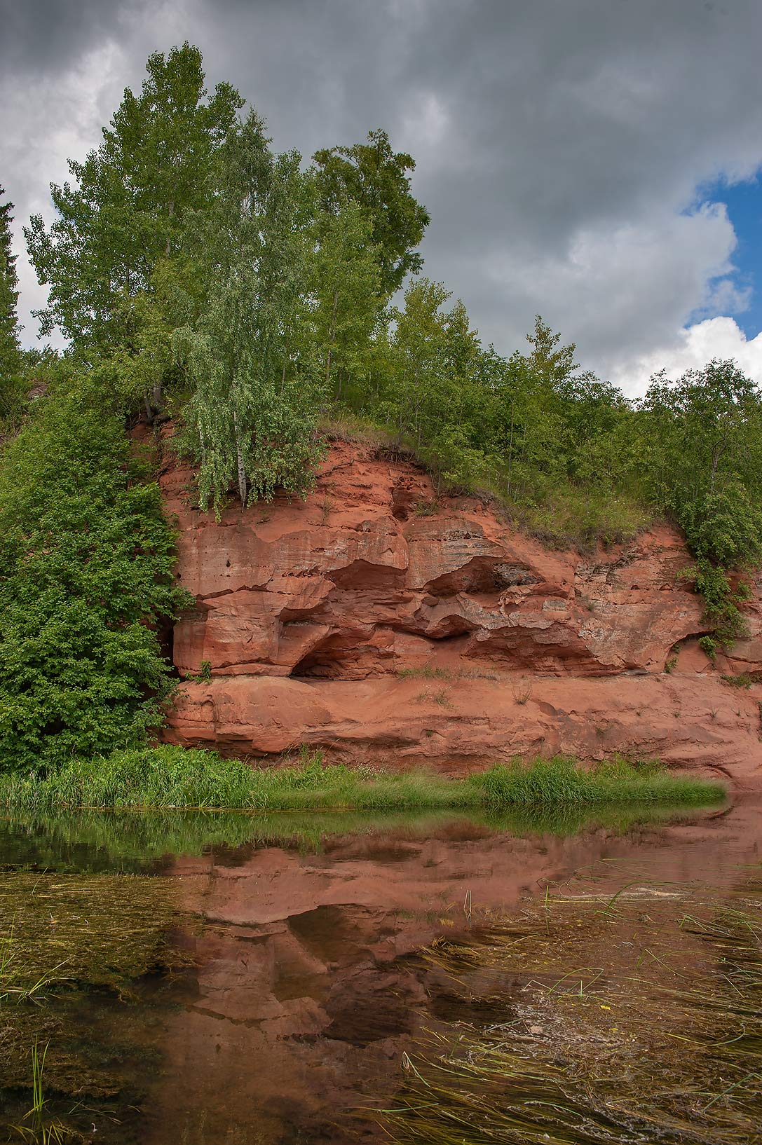 Red sandstone cliff near Oredezh River. Siverskaya south from St.Petersburg, Russia