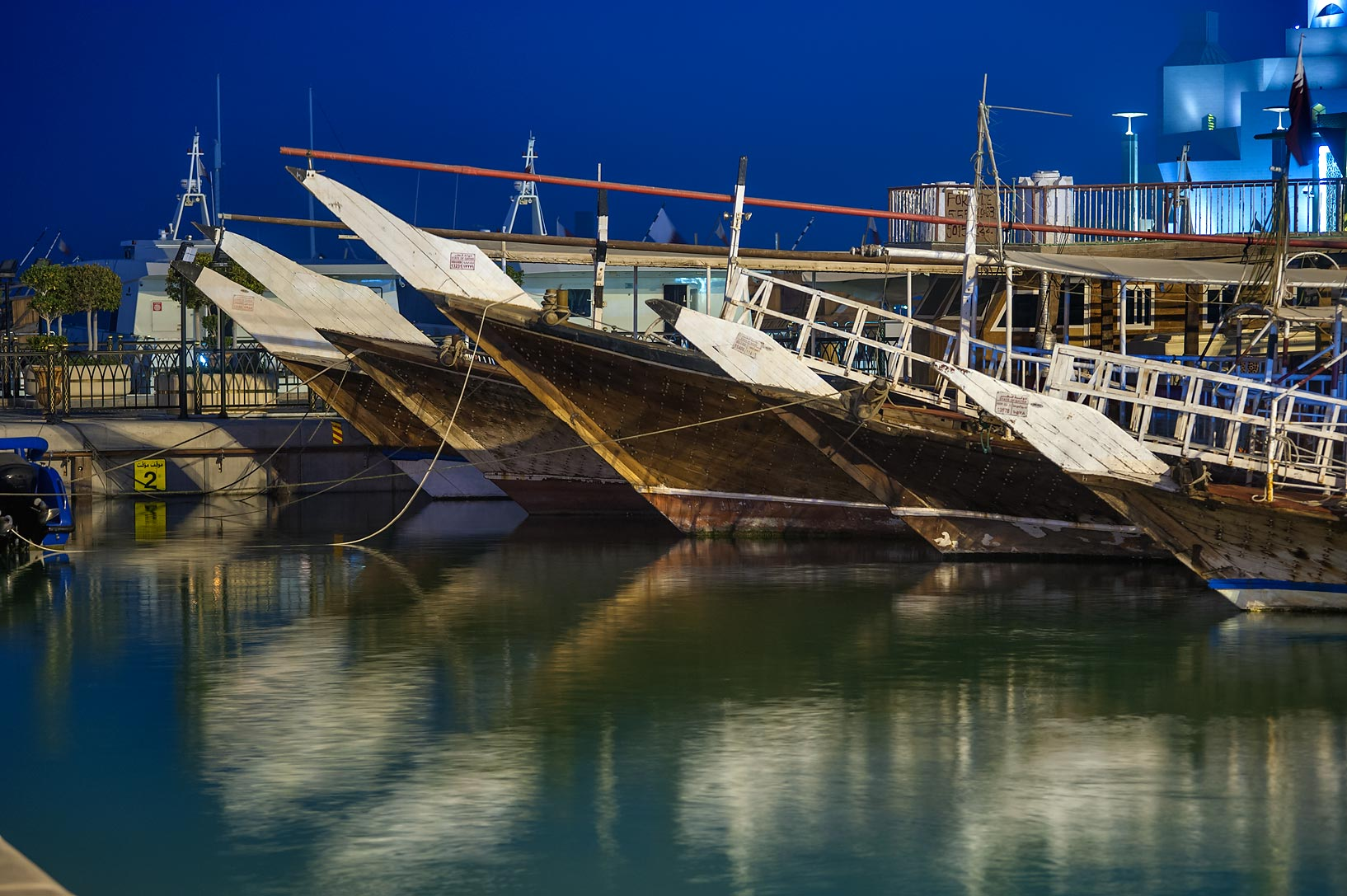 Prows of dhow boats at a marina, view from Corniche promenade. Doha, Qatar