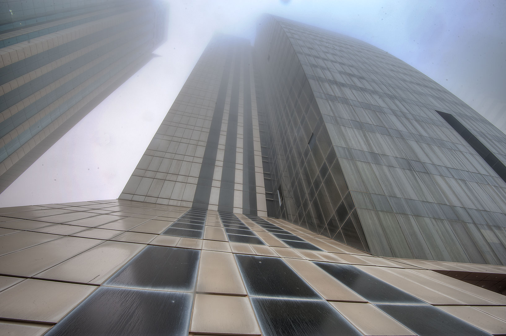 Foot of Abdulghani Commercial Tower in West Bay in fog. Doha, Qatar