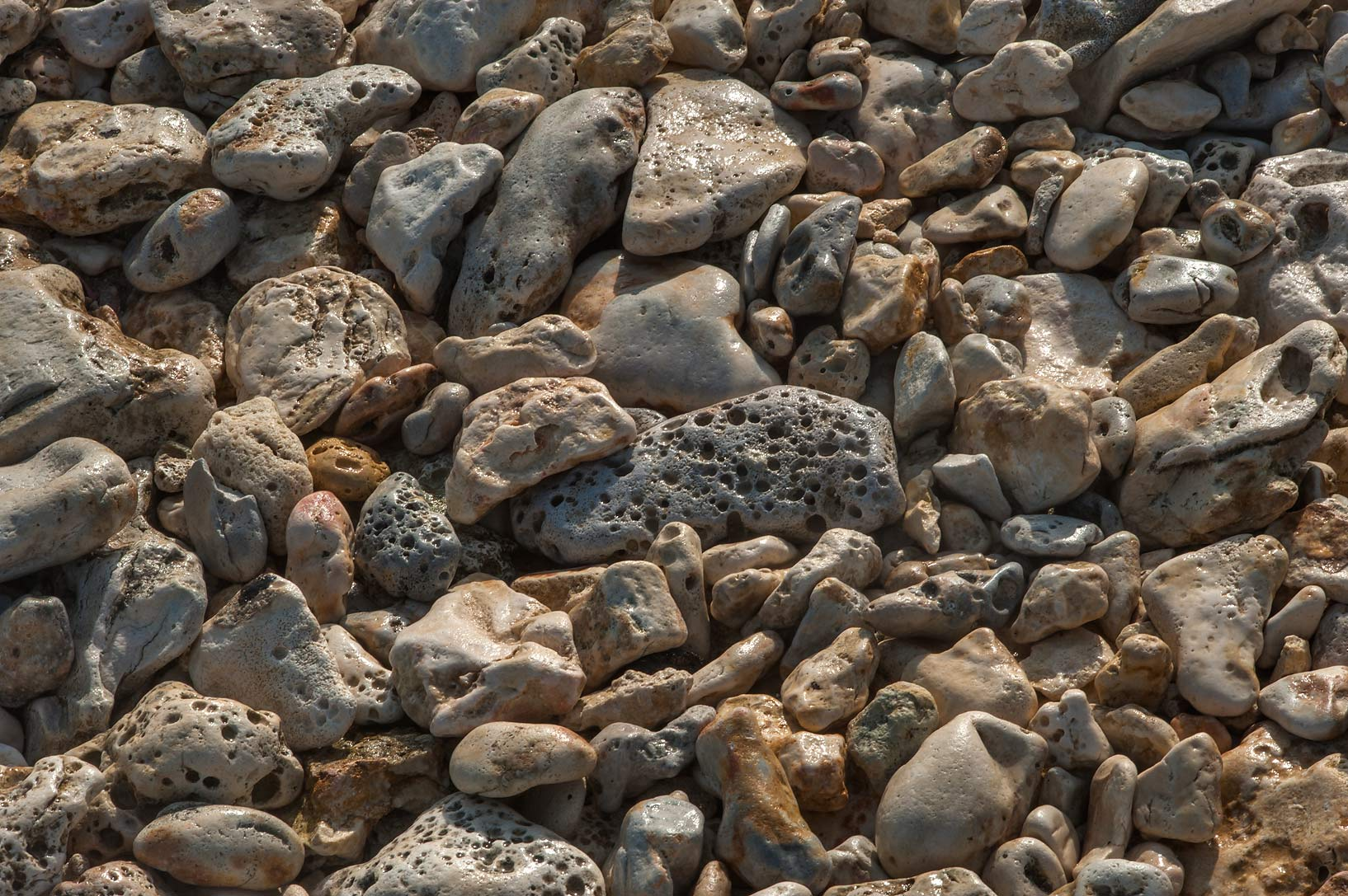 Pebbles on a beach below a rocky ridge of Jebel Fuwairit. Northern Qatar