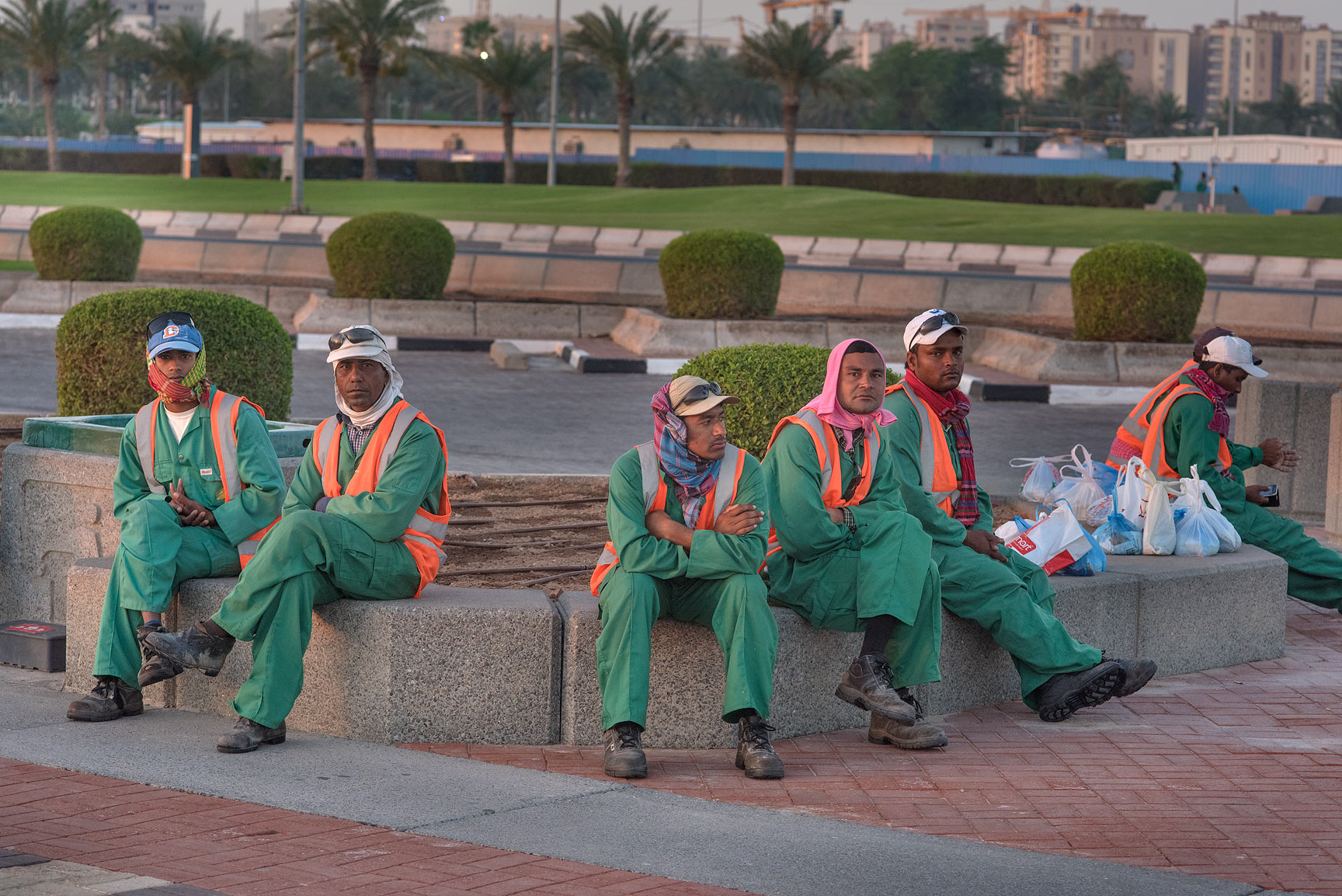 Workers resting on Corniche promenade at morning. Doha, Qatar