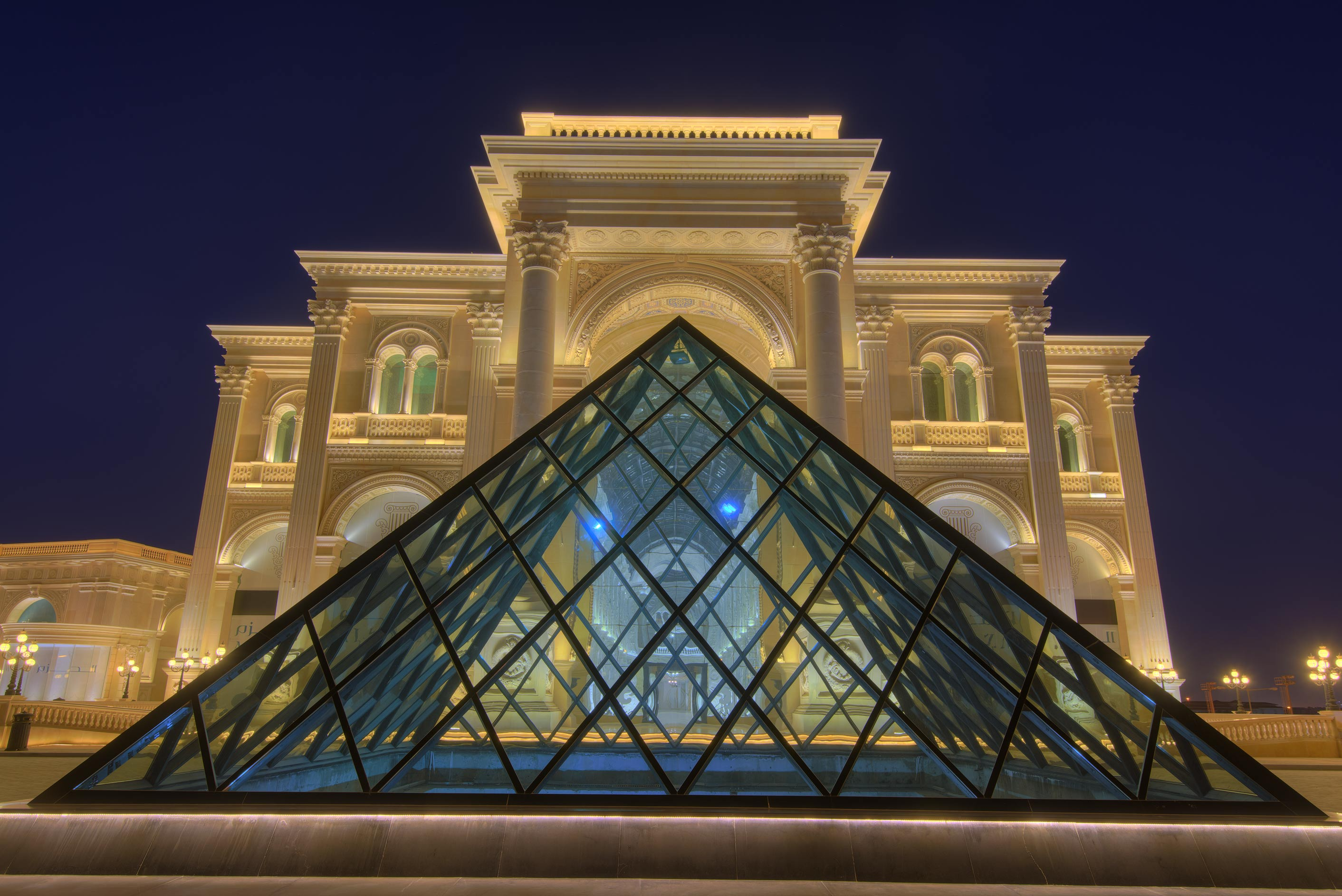 Glass pyramid at the entrance of Al Hazm Mall on Al Markhiya St. in dusk. Doha, Qatar