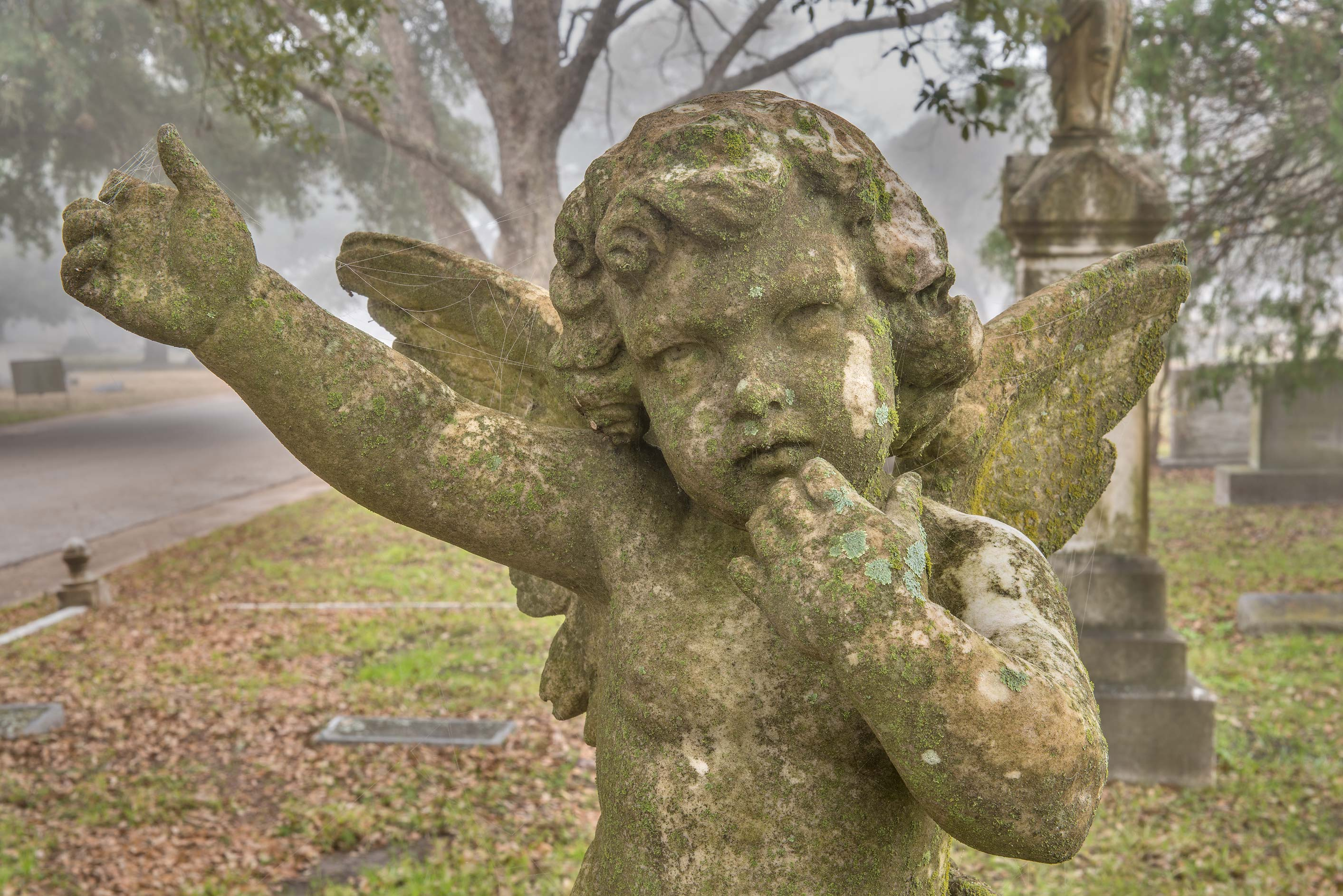 Old angel in fog in City Cemetery. Bryan, Texas