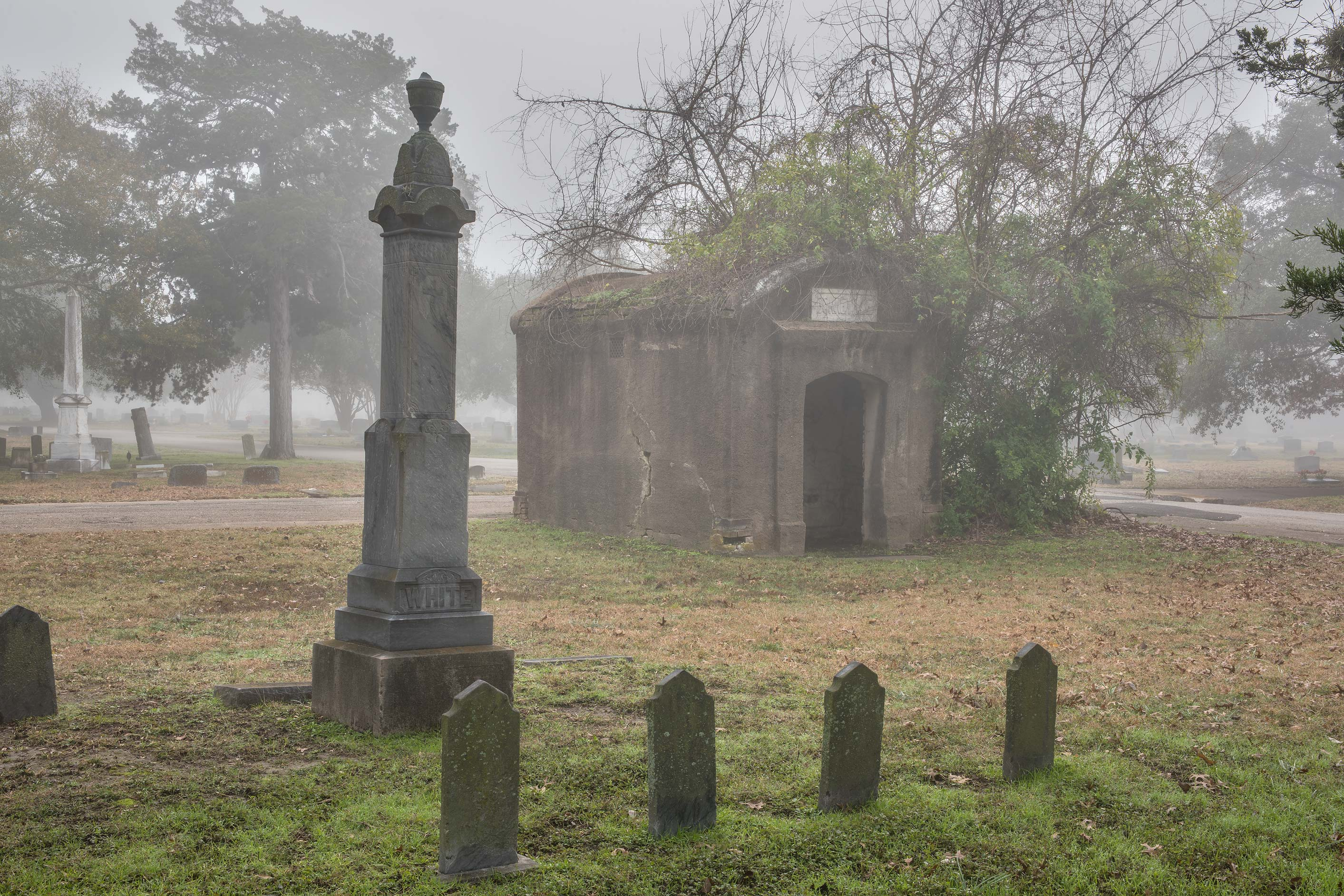 Tombs and a script in fog in City Cemetery. Bryan, Texas