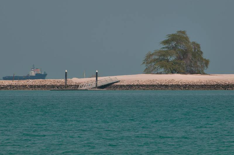 Palm Island with a lone mesquite tree (Prosopis juliflora) remaining from a resort mysteriously demolished in 2006 before Asian Games, view from Corniche. Doha, Qatar, March 25, 2011